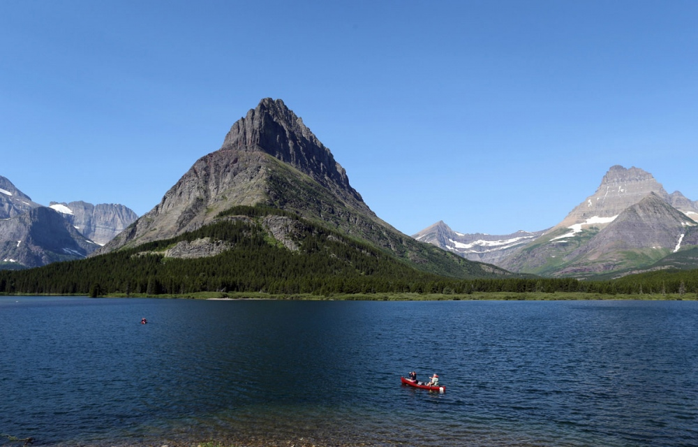 Kayakers enjoy a early morning ride and the scenery in the Swiftcurrent Lake, near the historic Many Glacier Hotel.