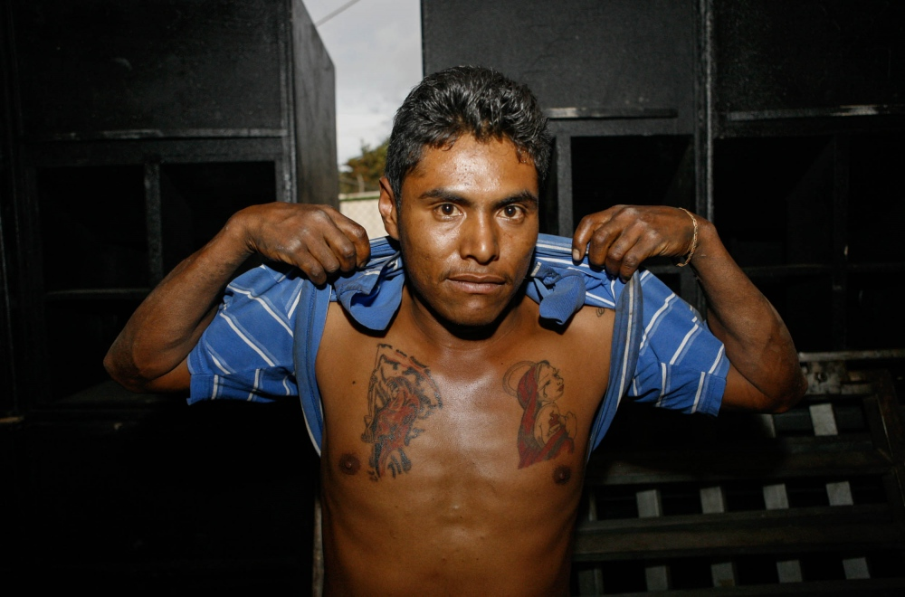 Helper of Sonido Pancho shows off his tatoos after setting up giant speakers. In one side the Holy Death and in the other a sexy Virgin. Peñon de los Baños, 2010.  //  Ayudante de Sonido Pancho muestra sus tatuajes despues de instalar bocinas gigantes. En un lado la Santa Muerte y en el otro la Virgen sexy. Peñon de los Baños, 2010.
