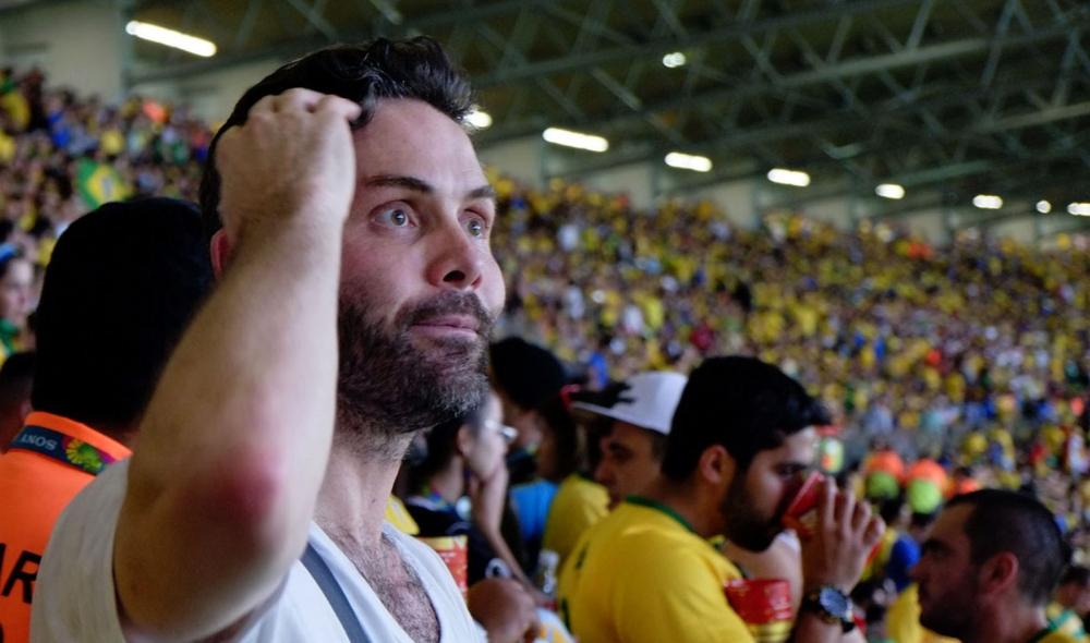 An unidentified Brazilian fan scratches his head in disbelieve of what is happening on the field below.