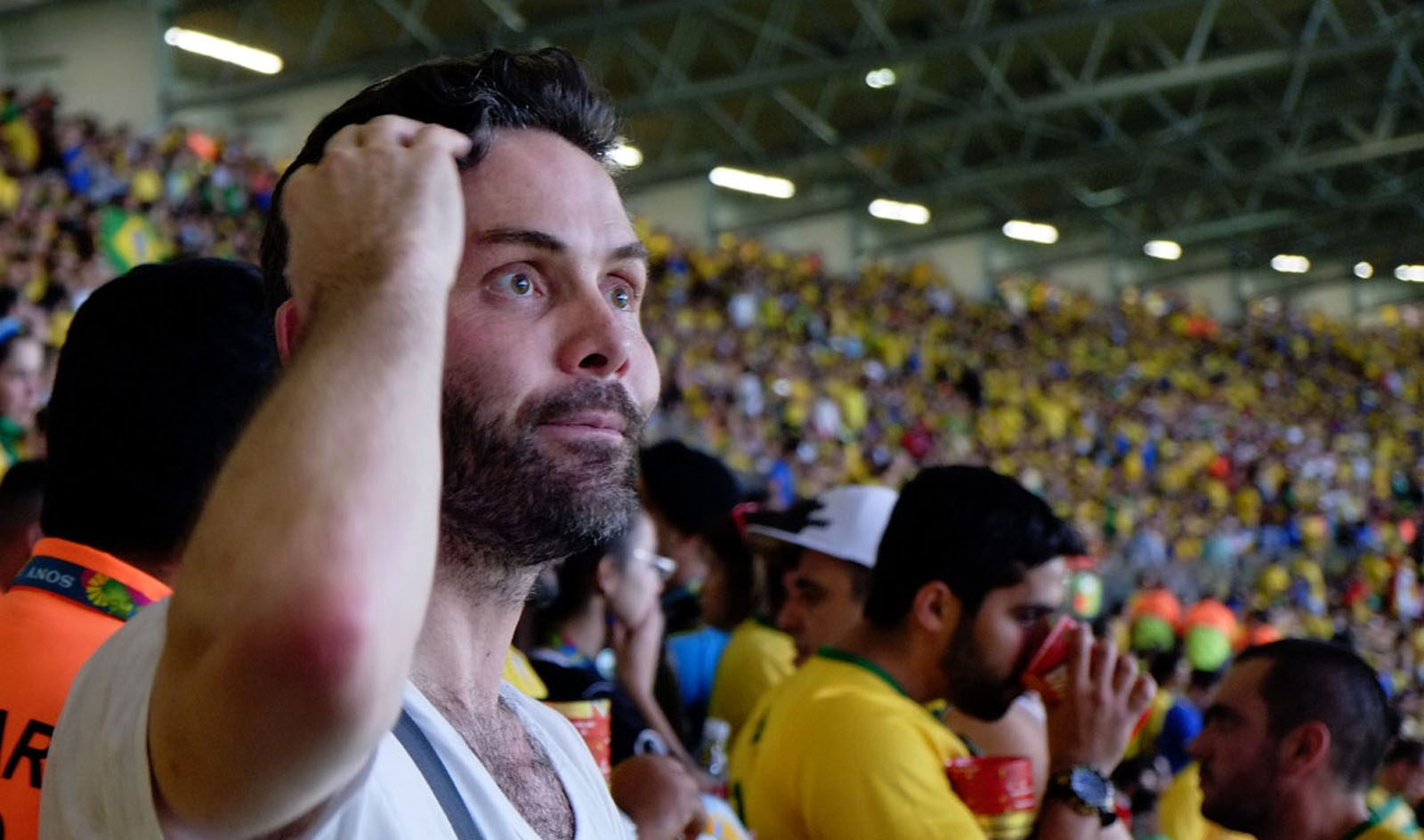 An unidentified Brazilian fan scratches his head in disbelieve of what is happening on the field below.