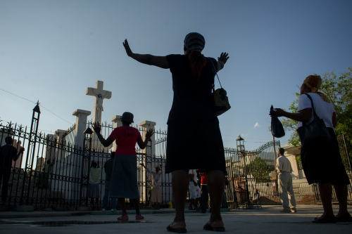 Church goers pray in front of the destroyed Cathedral of Our Lady of the Assumption April 15, 2011 in Port Au Prince, Haiti. Much of Port-au-Prince was demolished after a catastrophic 7.0 M earthquake, hit the island precisely in the town of Léogane, approximately 16 mi west of Port-au-Prince in Jan 12, 2010. Phot Ken Cedeno