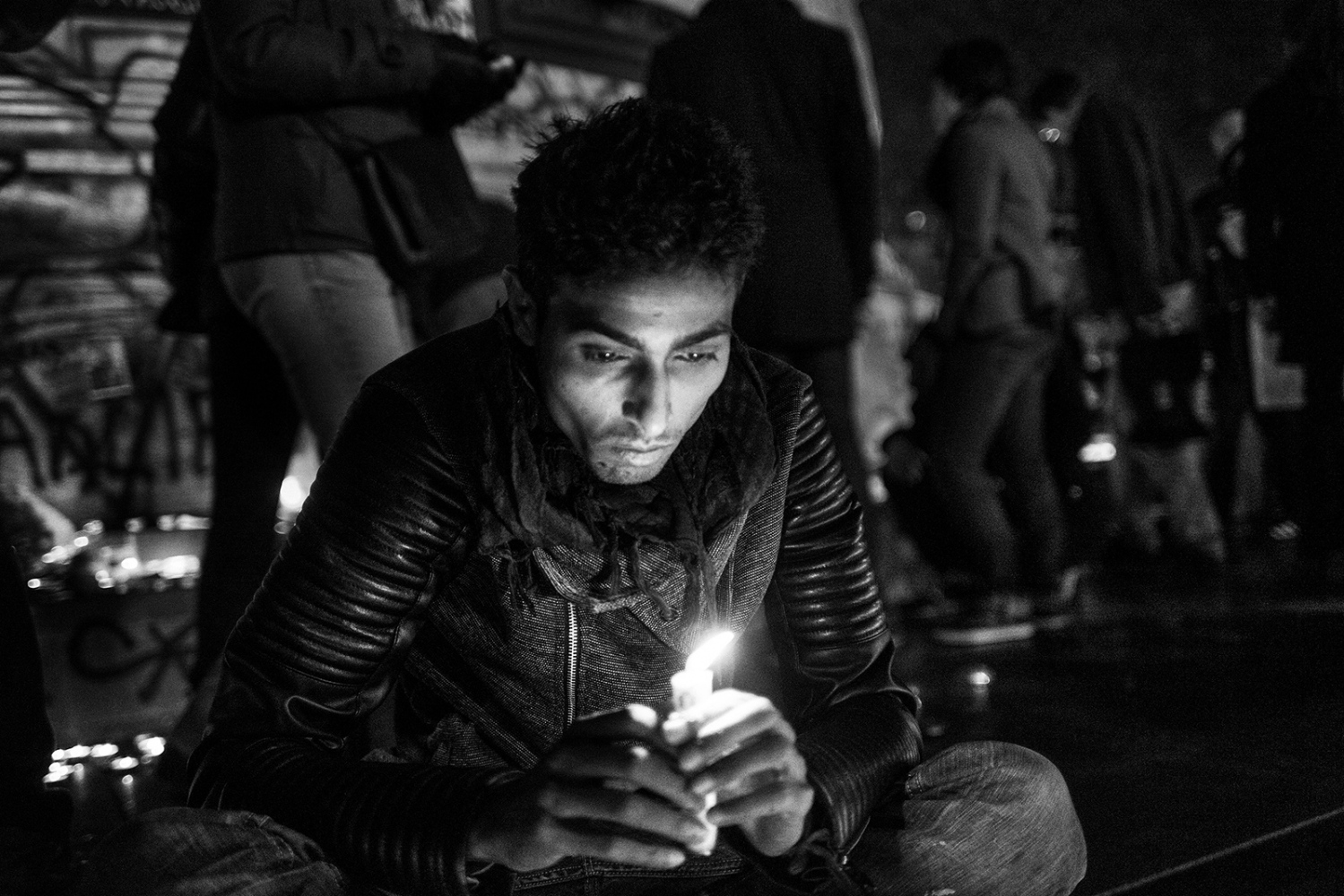Boy lights a candle in front of the statue in Place de la Republique. Paris, France, Place de la Republique. 14/11/2015. The aftermath of the terrorism attacks in Paris on 13/11/2015.Despite the ban on public meetings, many people gathered at the Place de la Republique to commemorate the victims of the terrorist attacks.