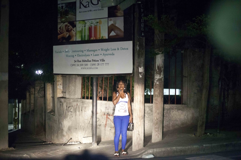 A sex worker waits for the arrival of guests in the streets of Petionville