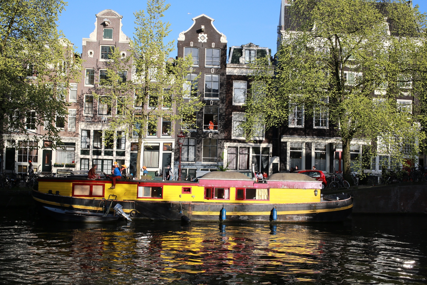 A young couple enjoy a glass of wine atop a house boat parked in one of the many channels around Amsterdam.