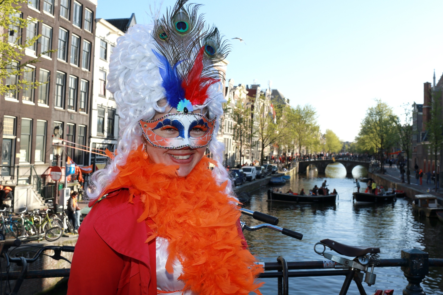 A unidentified reveler celebrates Koningsdag or King's Day on a bridge in Amsterdam.