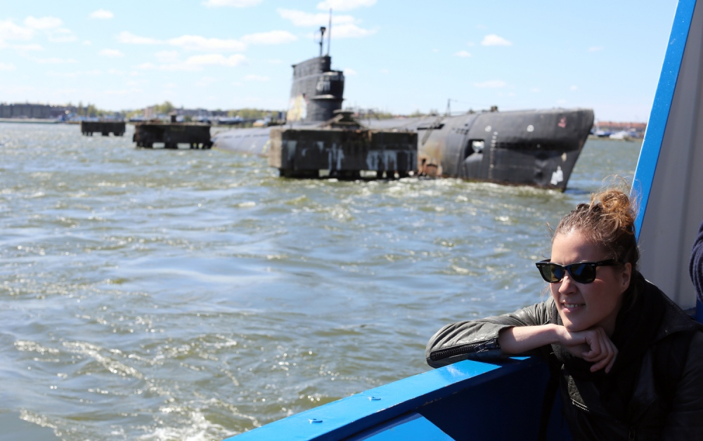 A young woman is seen on a ferry boat near an abandoned submarine north of Amsterdam.