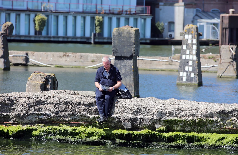 An elderlyman reads a magazine on a dyke near Amsterdam.