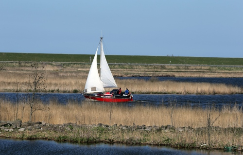 A sailboat navigates through a dyke on the town of Van Ewijcksluis, Nord Holland.