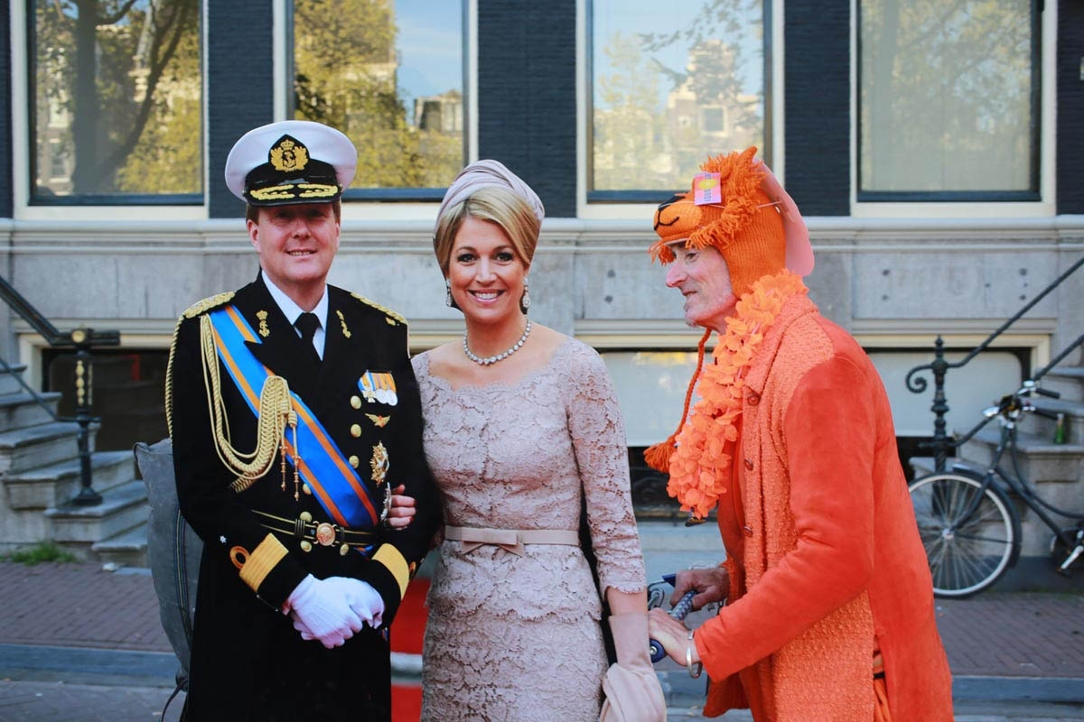 A Street Hawker pushes a cardboard cutout of the Netherlands new King Willem-Alexander and his wife Queen Maxima through the streets of Amsterdam.