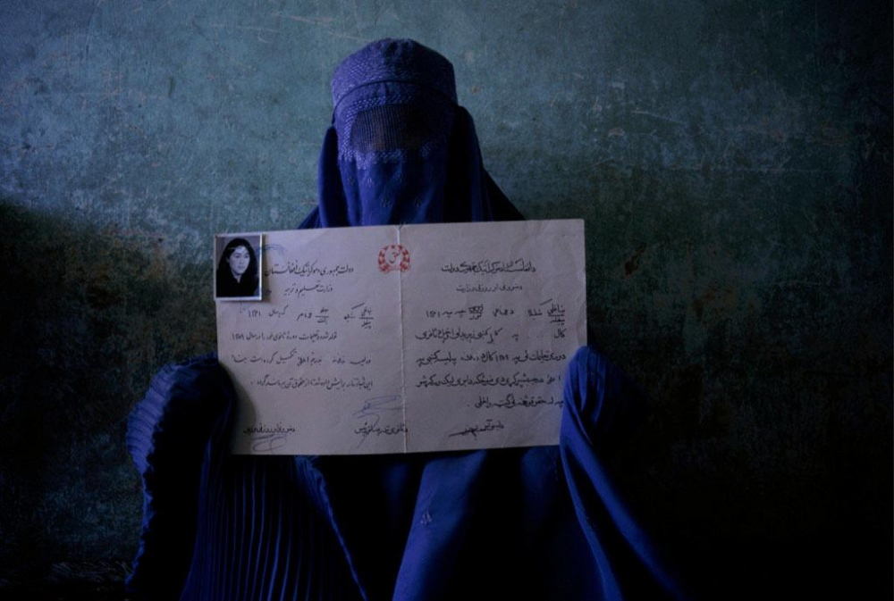 Kabul, 1998. A woman holds an earlier diploma. She had wanted to continue her education but the Taliban take over of Afghanistan in 1996 eliminated school for girls and women.