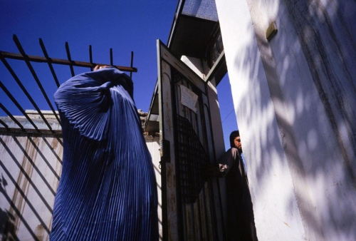Kabul, 1998. A woman enters a compound to attend a class about childbirth.