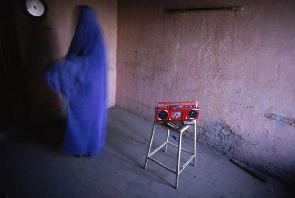 Kabul, 1998. A woman at home with a forbidden cassette player. When the Taliban seized power in 1996, music was forbidden.