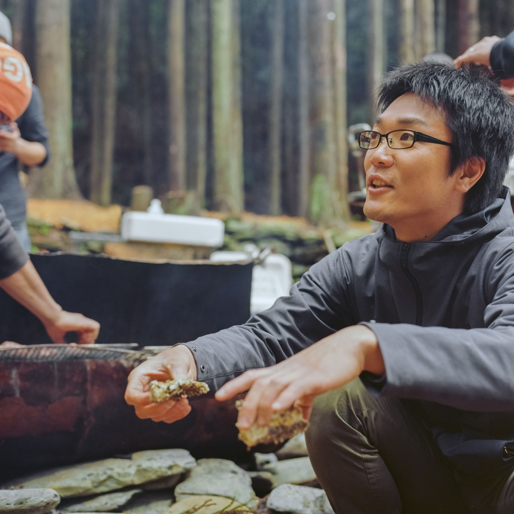 Kameyama Sensei (meaning teacher and in this case used as a title of respect) pauses during a team lucheon around a grill in the camp grounds of Hamagurihama. The project is working to develop a number of programs including camping and nature studies.