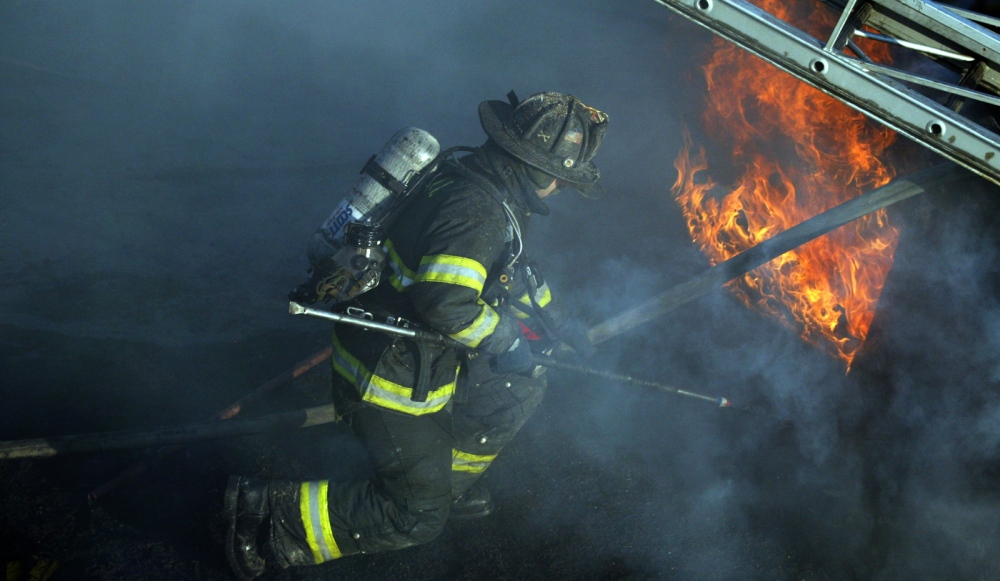 A firefighter works on a house fire in Astoria, Queens.
