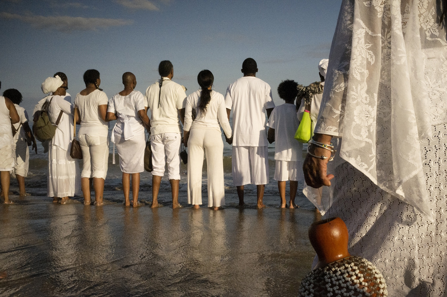 The Tribute begins on the boardwalk with speeches and African drumming. As sunset approaches, the crowd moves to the beach where they drum, dance, contemplate and pray. Participants are encouraged to dress all in white.   It took the slave ships between three weeks and three months to cross the Atlantic, depending on the winds. Estimates vary, but the consensus low range is that 10 to 15 million Africans made that crossing and that between 10 and 30 percent of them died in transit. That's two to five million people, perhaps many more, all of whom died horrible deaths from a brutal variety of causes. When you consider the numbers who died while being hunted or transported to the ships, the Middle Passage was a Holocaust that rivals, or even surpasses, the Holocaust perpetrated by the Nazi Germans and their allies in the early 20th century. #documentaryphotography #photojournalism #visura #burnmagazine #fujifilm #fujifilm_xseries #brooklyn #nyc #newyorkcity #historicnyc #coneyisland #coneyislandbeach #panafrican #panafricanism #blacklivesmatter #remembrance #melancholy #visualsoflife #beauty #middlepassage #tributetotheancestors