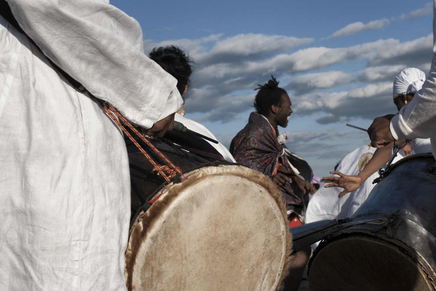 "The African drum circle is an integral part of the Tribute. The drums permeate the ceremony with alternating feelings of joy and melancholy. The beat is a physical thing that deepens the sense of awe and remembrance that falls over the crowd as the sun goes down. The African rhythms emphasize the relationship and continuity from the old continent and its vibrant religions to the people gathered in Coney Island to remember the victims of the Middle Passage. The drums also echo the rhythms of the ships and the seas, something the captives must have felt in their cramped spaces. They were packed in holds as tightly as inhumanely possible. The alloted space ranged between 6' x 1'4"" for an adult male to 4' 6"" x 1' for a young girl. A typical ship carried up to 600 captives. #documentaryphotography #photojournalism #visura #burndiary #canon #brooklyn #nyc #newyorkcity #historicnyc #coneyisland #coneyislandbeach #panafrican #panafricanism #blacklivesmatter #remembrance #melancholy #visualsoflife #drumcircle #africandrums #middlepassage #tributetotheancestors"
