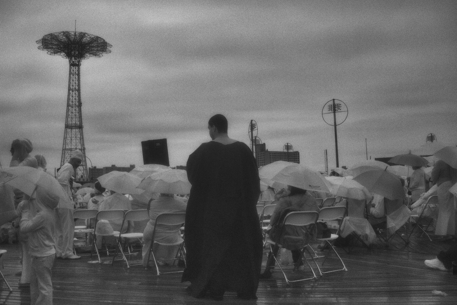 This image is one of the few I took on the boardwalk. It was a grey, rainy day and I was using my dedicated black and white camera. I liked the way the black-robed priest stood out against the white-clad crowd, with Coney Island's iconic Parachute Drop in the background and rain clouds filling the sky.