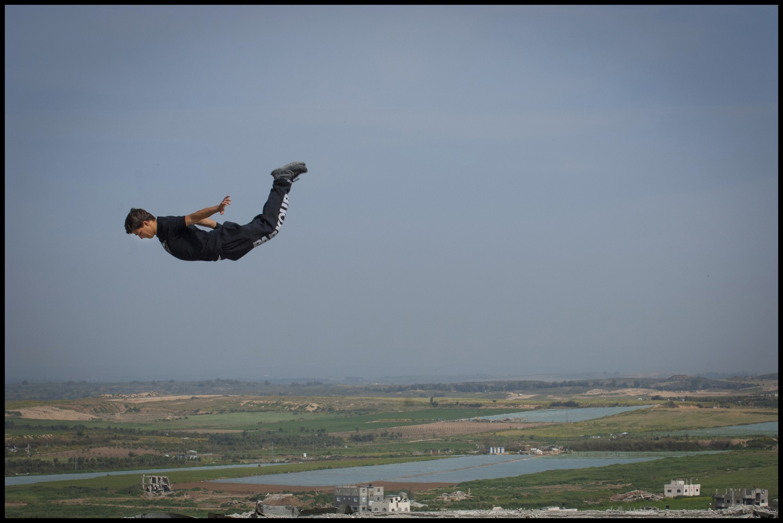 18 year old Fahed Dawood is airbourne over the Gaza Strip, Beit Hanoun, Northern Gaza Strip.  Fahed is a member of the Gazan Parkour team '3 Run Gaza'.