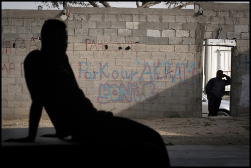 A passer by takes a look in at the door of the Parkour Teams centre while one of the '3 Run Gaza members,19 year old Saed Shaqura, takes a break.