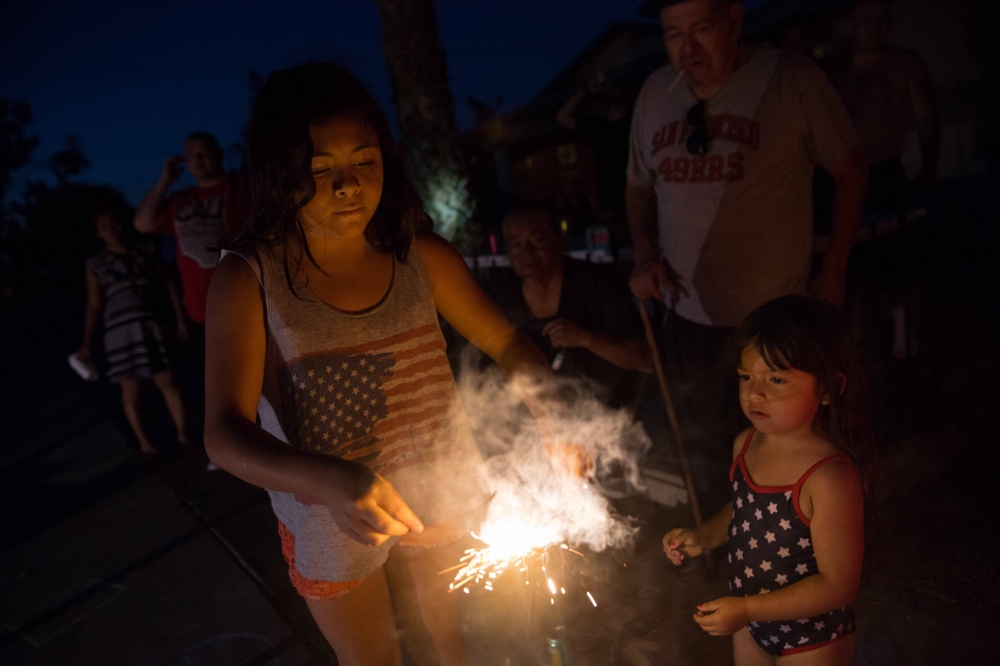 Hilda and Eliseo Garcia watch their grandkids light fireworks on Fourth of July in Tulare, California. She says she can't light any near her trailer for fear of starting a fire; the grass is too dry and there is no water source to fight flames. June 2016.