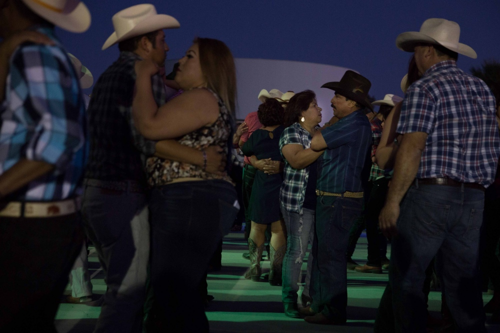 Juan Lomeli dances with his wife, Marielle, at a rodeo in Huron, California. Even though they had to move away from the predominately farmworking town due to a lack of work, they return often to see their friends and family. July 2016.