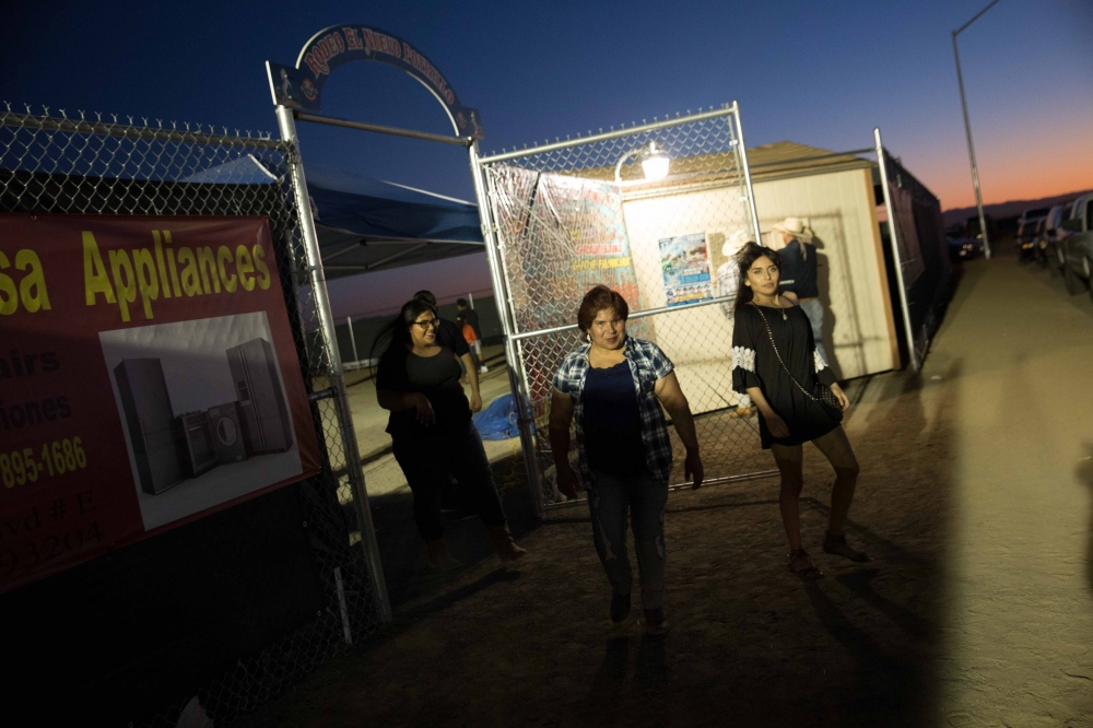 Marielle Lomeli, her daughter, and her neice, leave the Huron Rodeo after a night of watching bull-riding and dancing under the stars, and head to their new home in the Farming D Labor Camp, outside of Five Points, CA. Marielle tells me she hears of families leaving Huron for Arizona, Oregon, or Washington, even back to Mexico -- places where they hear jobs are more plentiful. July 2016.