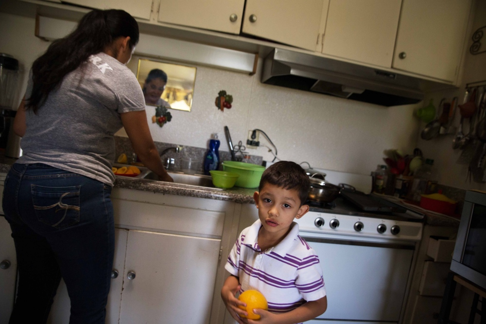 Lupe Vargas cleans oranges for her son, Emmanuel. The Vargas family and others in this community of mostly farm workers worry as they've watched the amount of work available decrease over the last few years. A combination of less water (leading to fallowed fields), mechanization, and changes in the types of crops grown in the region have all led to a decrease in the demand for farm labor throughout the Central Valley. June 2016.
