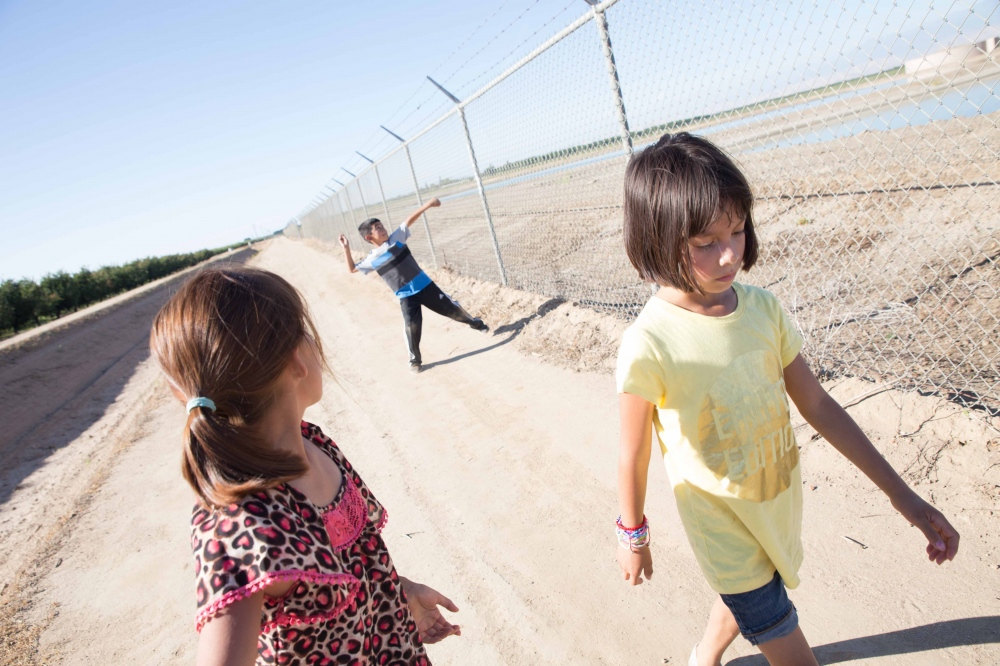 Kids walk in between a walled-off resevoir and an empty canal near their home in the Woodville Labor Camp, near Woodville, California. They remember playing in the canals years ago when they used to be full. June 2016.