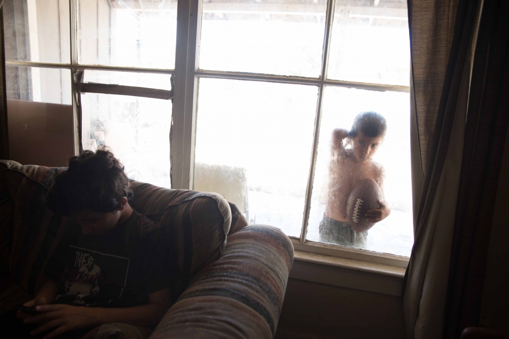 Gabriel Mendoza, 5, looks in the window of his home in Taurusa, California. The Mendoza's are one of seven families in Tulare County that have signed up for the California Drought Housing Relocation Assistance Program - a small number compared to the thousands of homes that have lost their wells. Because the assistance program is fairly new, many people don't know about it - and if they do, there are a lot of steps and paperwork to complete before being elligible for funds. June 2016.