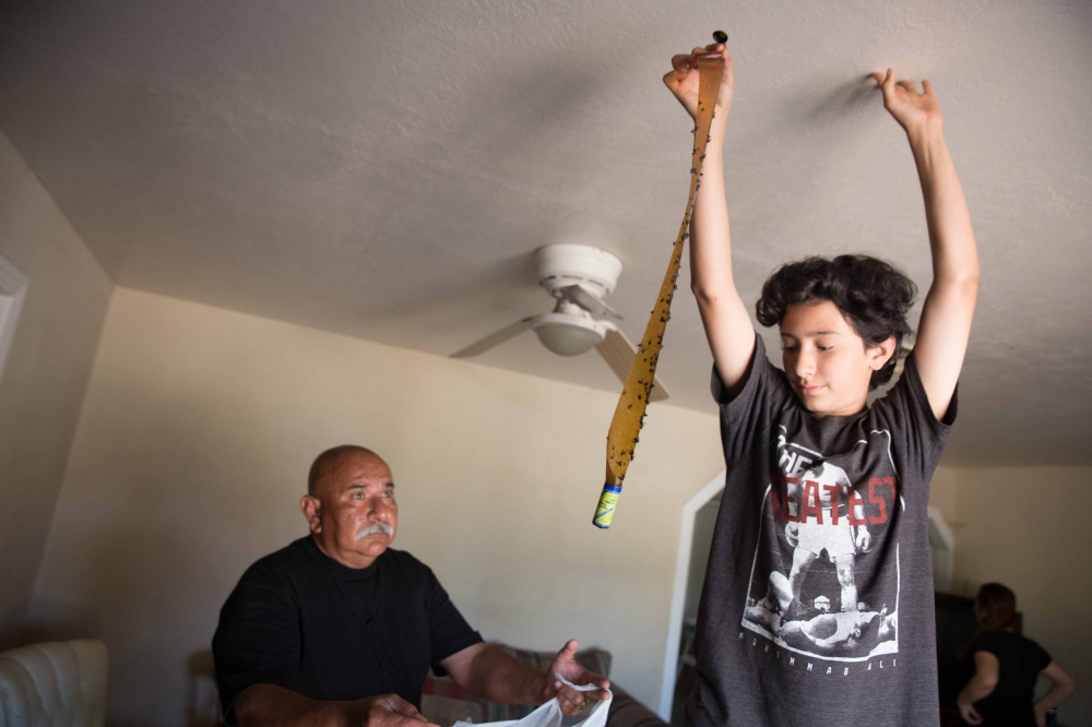Anthony Mendoza, 12, throws away a fly strip into a bag his dad is holding. Because their home in Taurusa, California, has been without water for over a year, their sewage system is backed up and attracts flies. June 2016.