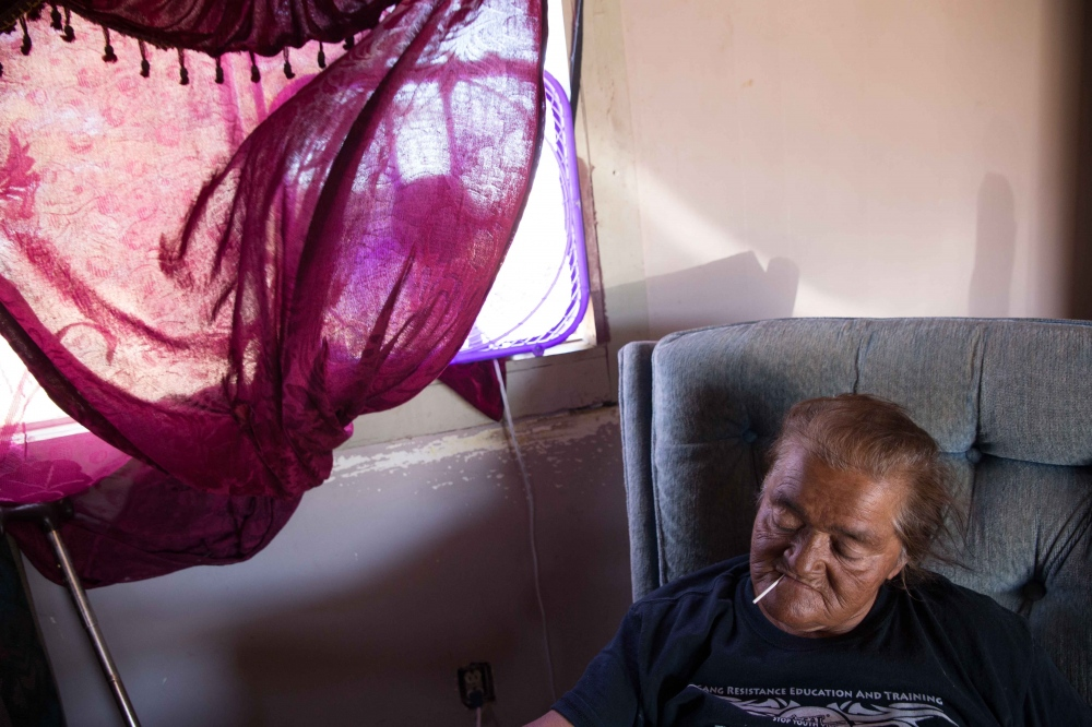 Hilda Garcia sits under a fan, trying to keep cool on a triple digit day in Okieville, CA. June 2016.