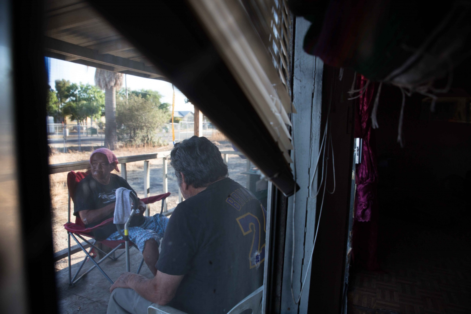 Hilda and Eliseo Garcia sit on their front porch with wet towels to cool off from the intense summer heat. It's not unusual for the temperature to stay in the triple digits for days, sometimes weeks. June 2016.