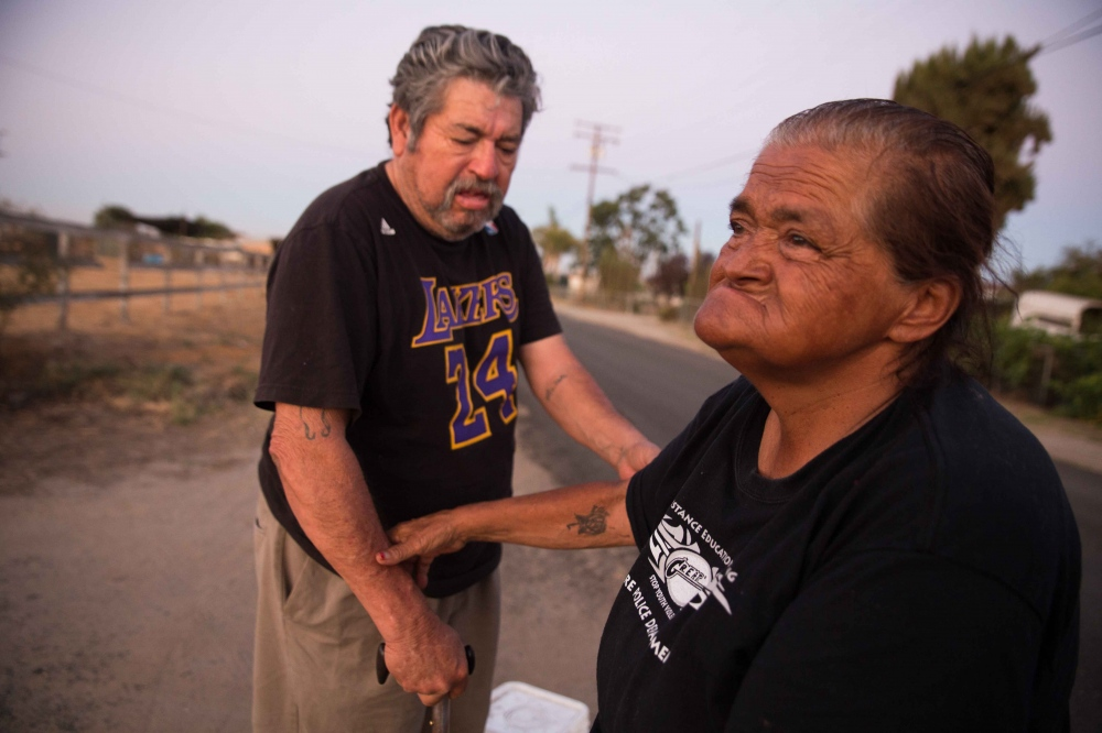 "Hilda Garcia holds the arm of her husband, Eliseo, as they wait for a ride to the town of Tulare, 8 miles away, to fill up water jugs. In early June, they moved into a trailer that had no running water since the well on the property had dried up. ""You can't do without water, it's very very hard. It makes me cry,"" says Hilda. June 2016."