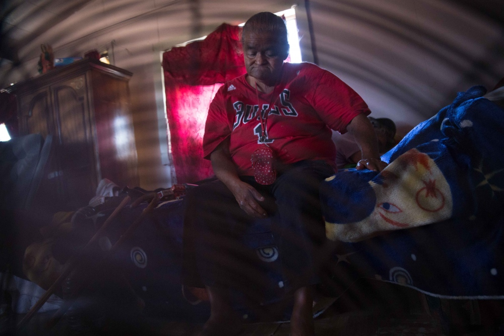 Hilda Garcia sits in front of a fan in her trailer in Okieville, California. She has a swamp cooler, but no water to put in it to keep cool. June 2016.