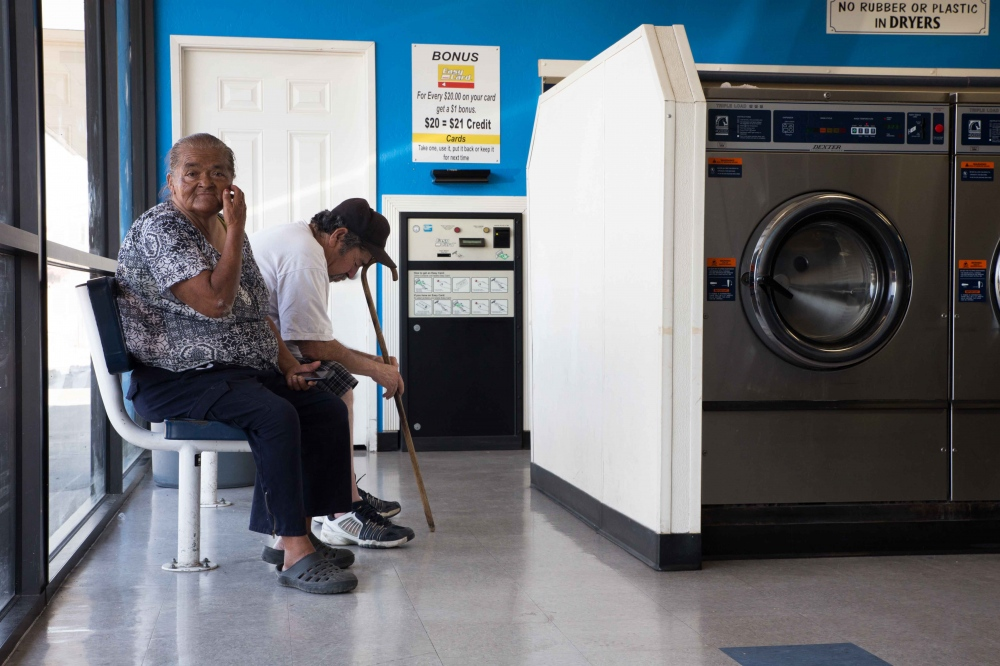 "Hilda and Eliseo Garcia wait for their laundry in Tulare, California. ""My washer works [at home] but we got no water there, that's the problem!"" she says. June 2016."