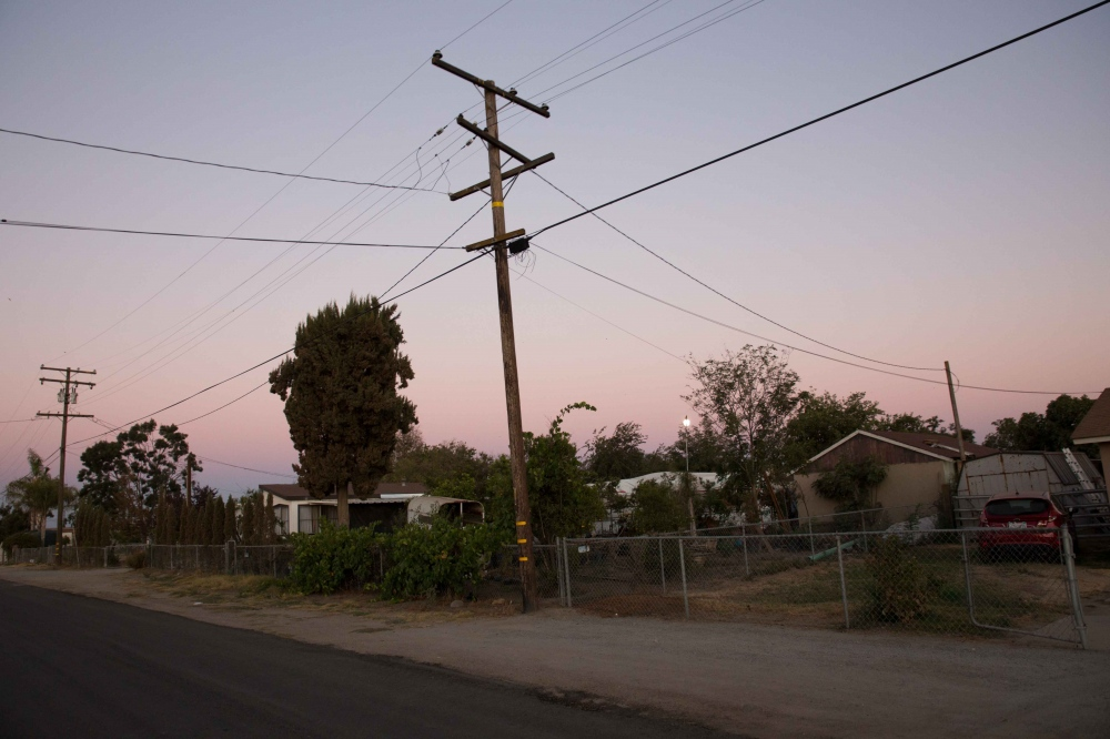 Dusk in Okieville, California. Most of the residents of Okieville, which include both Dust Bowl migrants and Hispanic farmworkers, have wells that have gone dry, with more wells expected to go dry in the near future. Hoses criss-cross the streets, delivering precious water from one house to another, and green water tanks sit on almost every brown lawn. July 2016.
