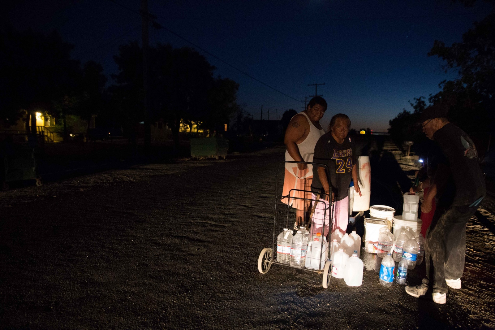 "Hilda Garcia and her family fill up their various jugs and buckets from a neighbor's hose as night falls in Okieville, California. ""This is how we fill water,"" says Hilda, ""A lot of hassle, huh? You do what you got to do when you're homeless and got no water."" July 2016."