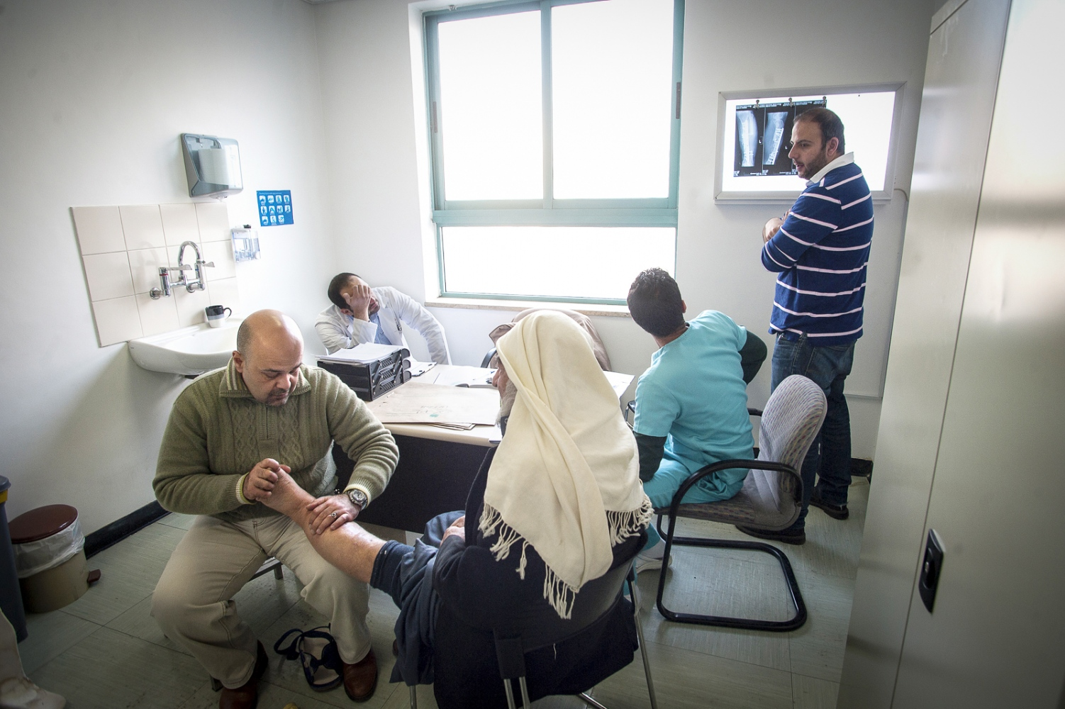 43 year old Iraq born Orthopedic Surgeon Dr Ali AlAni examines a patient to access the ongoing treatment that might be required, He's accompanied by Jordanian GP Zaid Sabeeleish, Physiotherapist Saleem Omar and fellow Orthopedic Surgeon Hanna Janho all from Amman in Jordan.