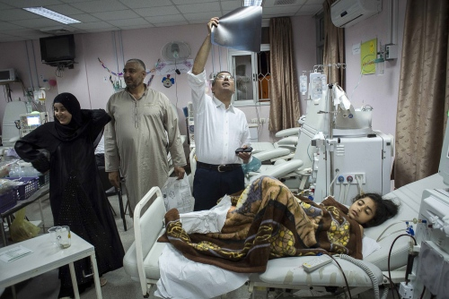 9 year old Fatma Othman undergoing dialysis the night before her kidney transplant operaton at the Al Rantisi Hospital's child dialysis ward. Her mother Marwa (pictured far left with her husband Osama) is donating her kidney to her daughter. British sugeon Dr Abdul Hammad examines Fatma's X-ray and undertakes a final check on his patient.