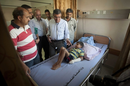 "9 year old Abdel Motalib Awad  is examined by British Surgeon Abdul Hammad accompanied by fellow surgeon from The Royal Liverpool University Hospital Sanjay Mehra (British/Indian dual nationality) and accompanying Gazan doctors and surgeons.  Abdel caused particular concern to the Surgical team due to his young age and small size, stunted due to kidney failiure. Nearly all his veins had collapsed from the dialysis treatment. The last remaining vein in his left arm was also beginning to fail as can be seen by the swelling. ""If we don't operate this boy won't last another six months"" stated Surgeon Abdul Hammad in conversation out of ear shot of the boy and his relatives. He will be undergoing a kidney transplant operation the next day. His mother Sharifah being the donor and best match from tissue typing tests. At the Al Shifa Hospital in Gaza City."