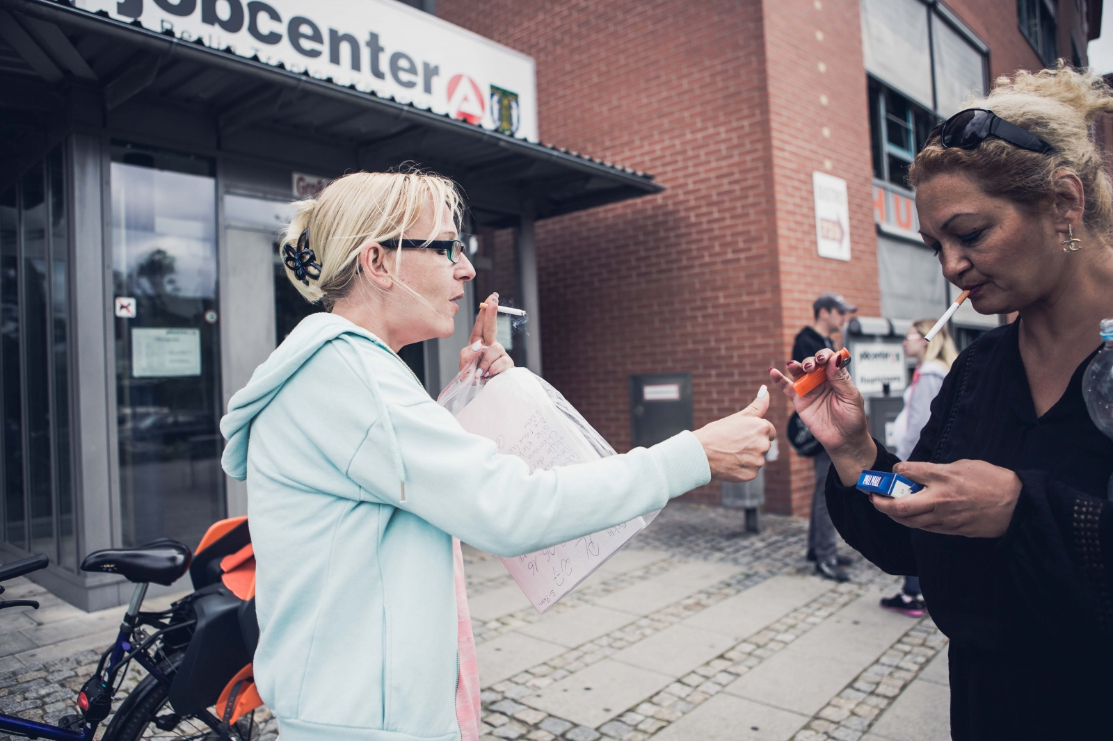 Claudia B., 37, shares a smoke with another woman in front of the jobcenter in Berlin, GERMANY, on June 27, 2016. Claudia receives the so-called Hartz-IV unemployment social benefit. This day she applied for furniture money for her new apartment.