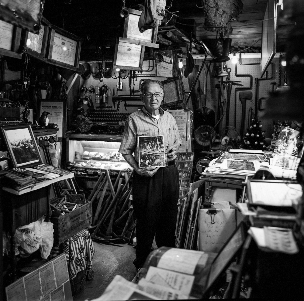 Retired Coal Miner, Lykens, Pennsylvania 2010  90-year-old retired miner who has a small museum of mining memorabilia in his garage, holding a 45-year-old photograph showing himself and others attempting to rescue trapped miners after an underground cave-in. His brother died in that accident.