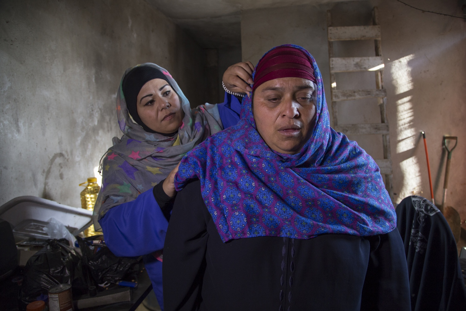 Fatima Castañeda helps Maria Luna fix her hijab at Maria's humble house. Maria Luna and her 8 year-old son Israel share a bed in a cold dark room next to a stable in Rosarito, Mexico. Luna wakes up at 5am every day to feed the horses and clean the horse manure. In exchange for her work, they pay her 200 pesos (approximately 12 USD) and let her and her son stay in the room. Maria converted to Islam only 2 months ago, which represents a very small percentage of the community in Mexico.