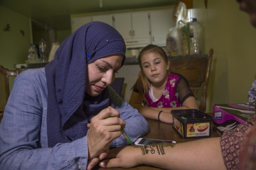 Iman Abi applies henna to Fatima Castañeda's hands at a mendhi party hosted by a muslim friend to celebrate Fatima's upcoming wedding.