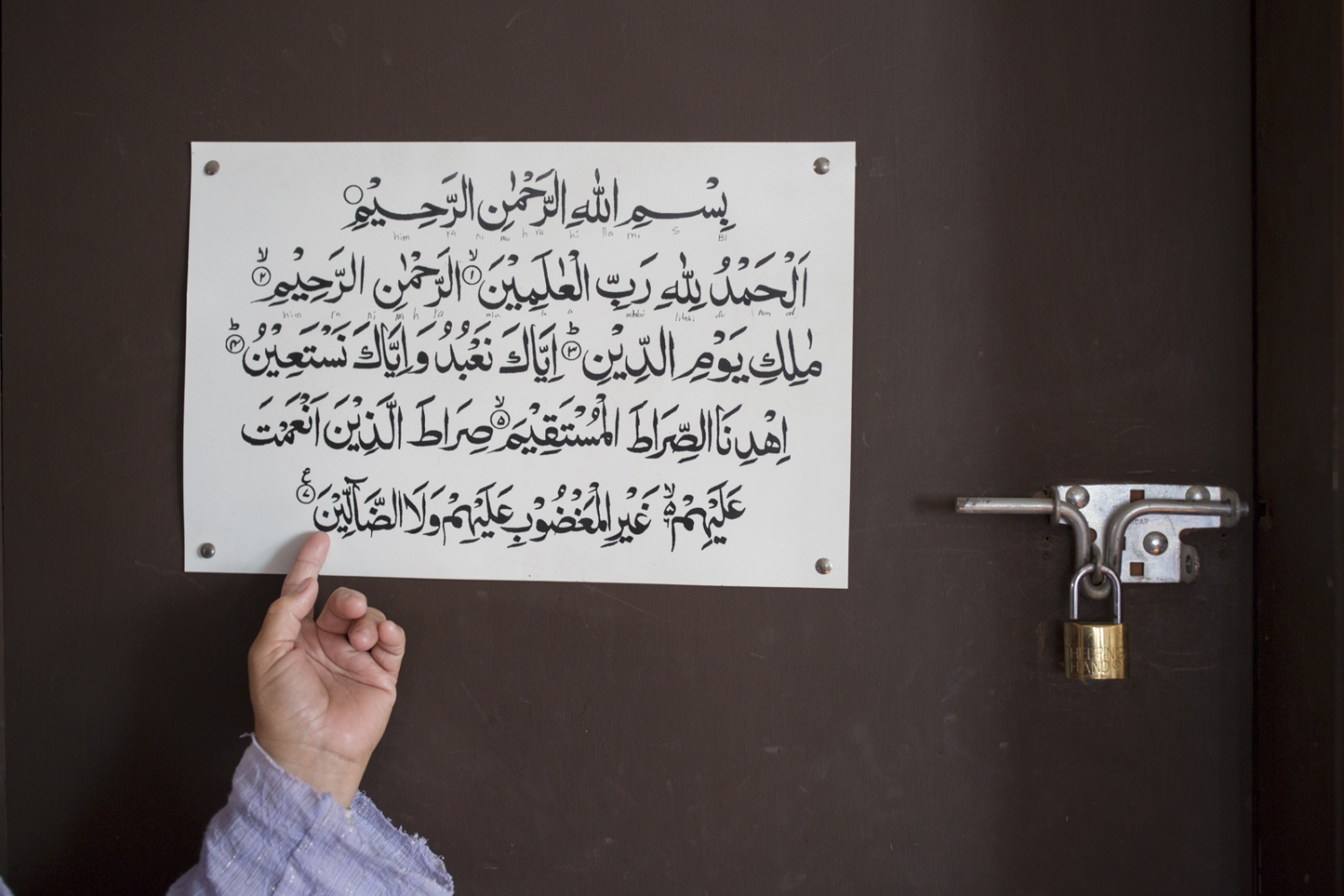 Irma Morales shows a sign with a text from the Koran at her daughter's house in Rosarito, Mexico.