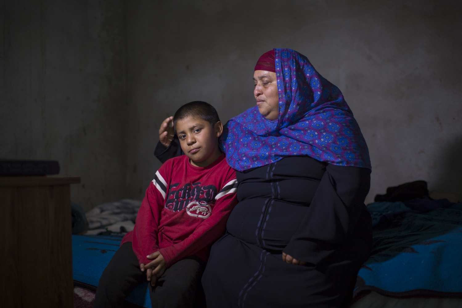 Maria Luna and her 8 year-old son Israel sit on the bed that they share in the cold dark room where they live next to a stable in Rosarito, Mexico. Luna wakes up at 5am every day to feed the horses and clean the horse manure. In exchange for her work, they pay her 200 pesos (approximately 12 USD) and let her and her son stay in the room. Maria converted to Islam only 2 months ago, which represents a very small percentage of the community in Mexico.