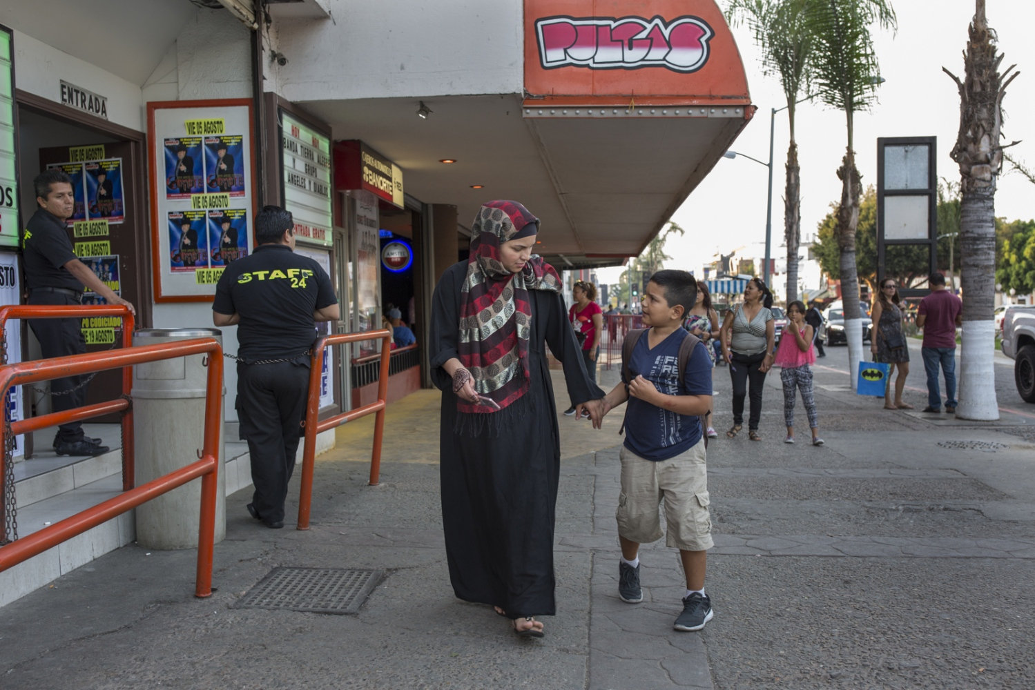 Keridma Loaeza and her son Ivan walk down the Revolution Street in downtown Tijuana, cluttered with bars, restaurants and clubs.