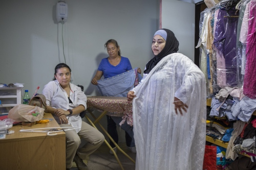 Fatima Castañeda tries on her wedding dress who has been made from scratch for her in a little boutique in Rosarito, Mexico.