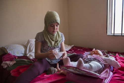 Nahomi Castañeda, 10, plays with her doll baby in her mother's bedroom in Rosarito, Mexico. She converted to Islam 5 years ago at the same time as her mother and older brother Carlos.
