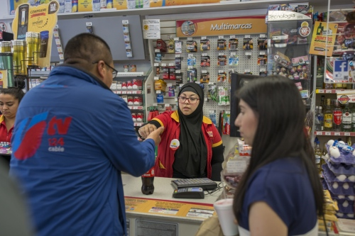 Zaira Galaviz helps a customer at the convenience store where she works as a cashier.